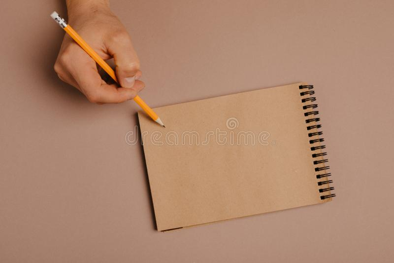 Hand writing in notepad using a pencil, on gray background.  royalty free stock image