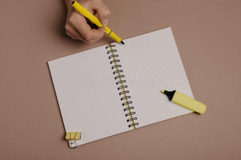 Hand writing in notepad using a pen, on gray background. Hand writing in notepad using yellow pen, on gray background royalty free stock photography