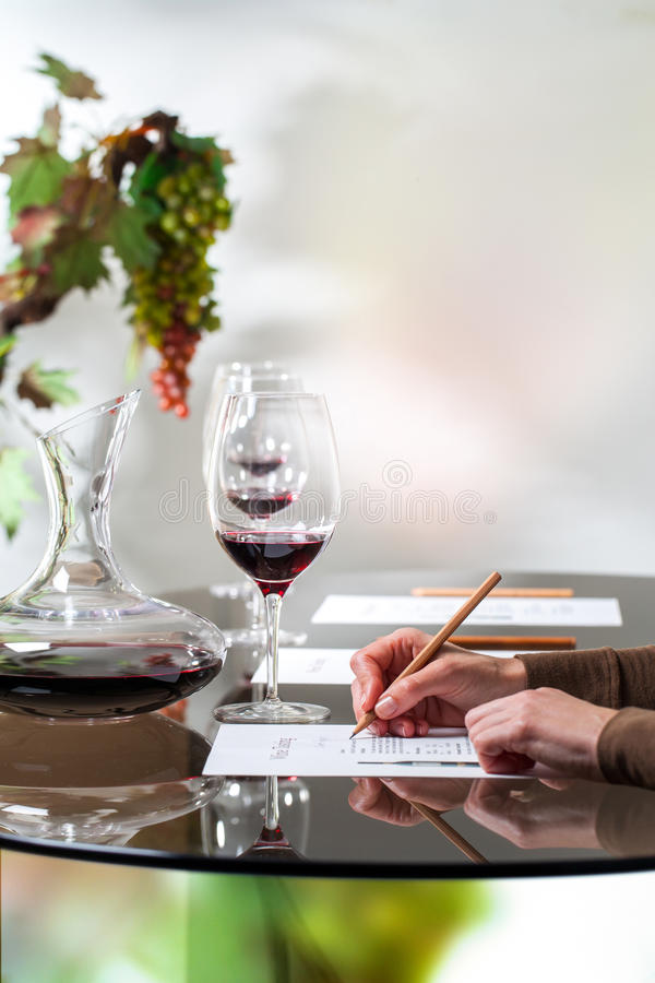 Hand writing on paper at wine tasting. Macro close up of female hand writing notes on paper at wine tasting stock images