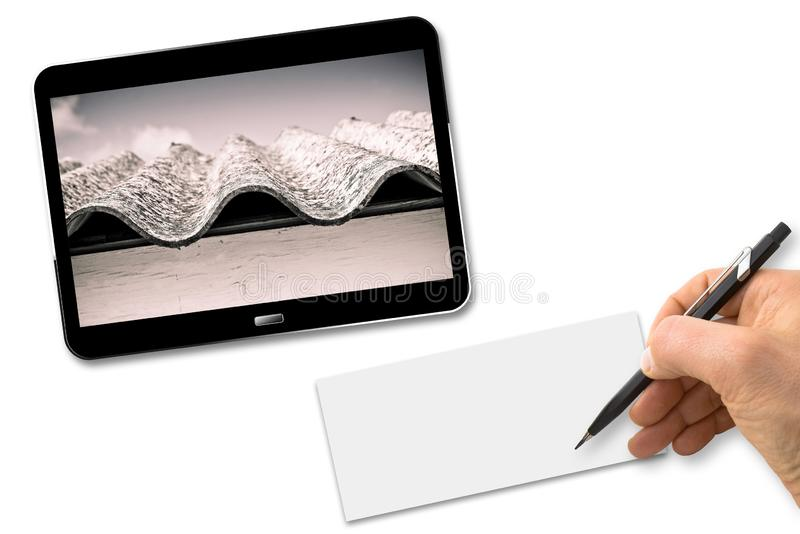 Hand writing with a pencil on a blank sheet above a white desk with a digital tablet showing a dangerous asbestos roof - Concept stock image