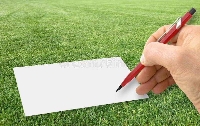 Hand writing with a pencil on a blank sheet over a beautiful green mowed lawn - concept image with copy space stock images