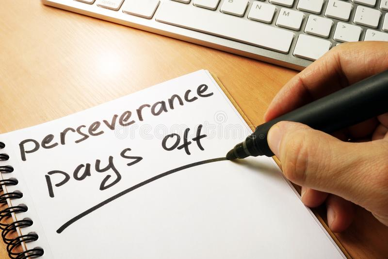 Hand is writing perseverance pays off. stock image