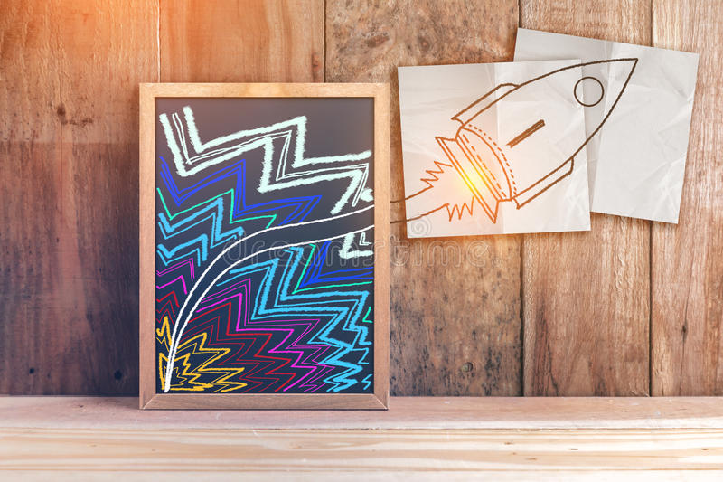 Hand writing rocket on white paper and chalkboard stock image