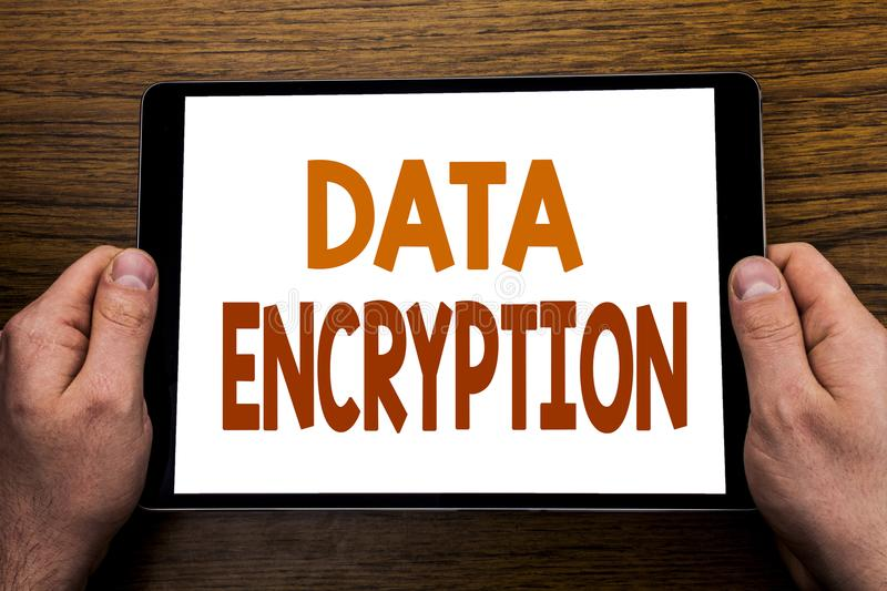 Hand writing text caption Data Encryption. Business concept for Information Security Written on tablet laptop, wooden background w. Hand writing text caption stock images