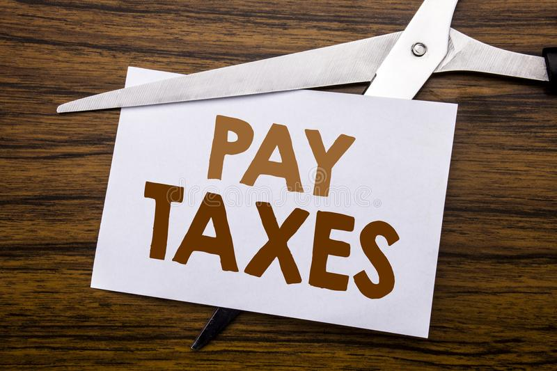 Hand writing text caption inspiration showing Pay Taxes. Business concept for Taxation Overtax Return Written on note, wooden back. Hand writing text caption stock image