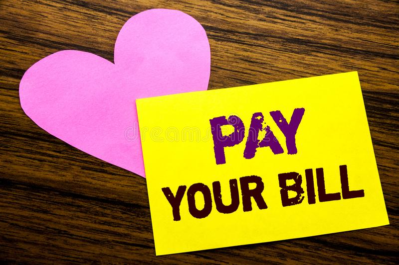Hand writing text caption inspiration showing Pay Your Bill. Business concept for Payment for Goverment written on sticky note pap. Er, wooden background. With stock photo