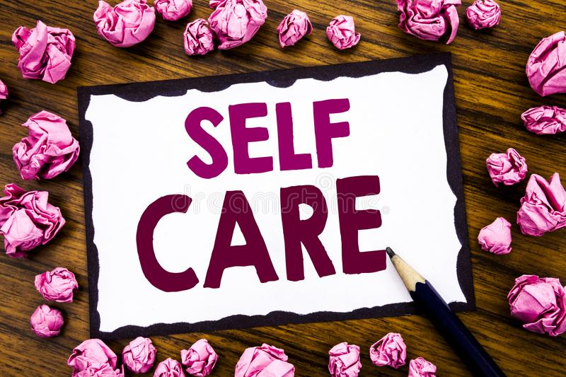 Hand writing text caption inspiration showing Self Care. Business concept for Taking caring for own Health Written on sticky note. Paper, wooden background stock image