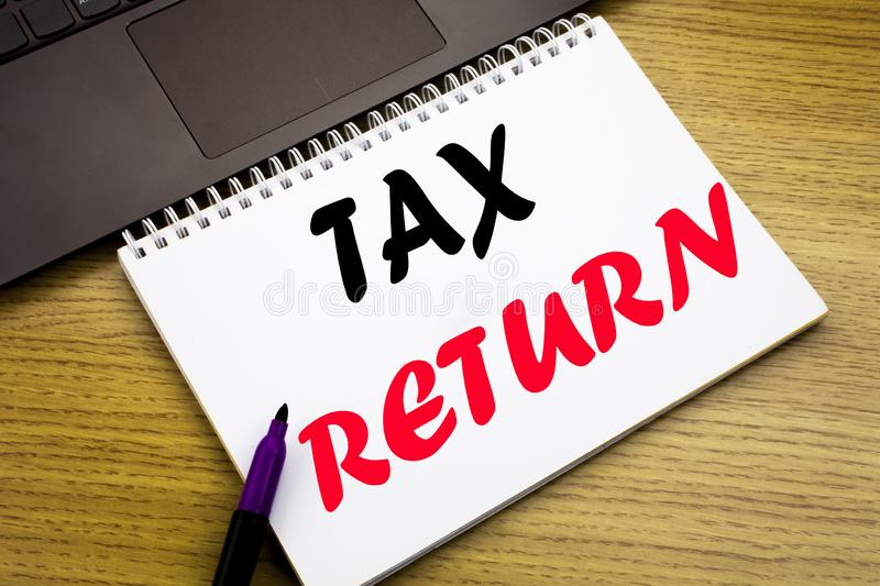 Hand writing text caption inspiration showing Tax Return. Business concept for Accounting Money Return written on notebook book on. Wooden background in the royalty free stock photography