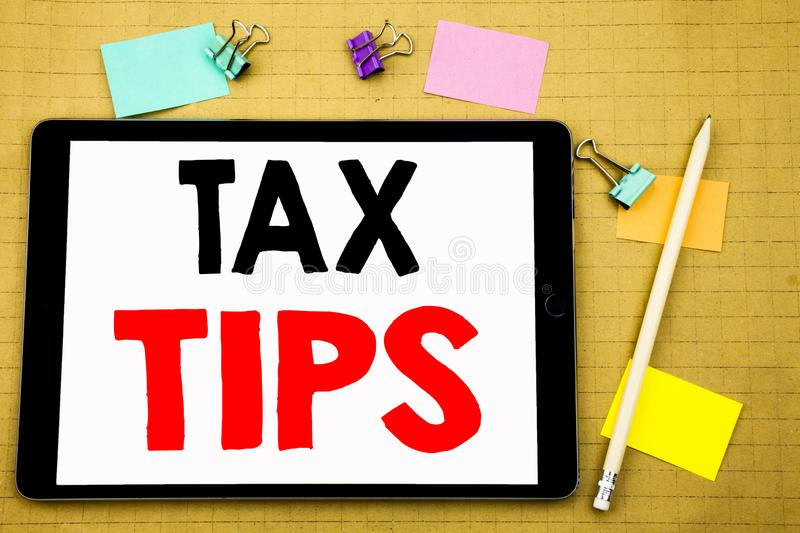 Hand writing text caption inspiration showing Tax Tips. Business concept for Taxpayer Assistance Refund Reimbursement Written on t. Ablet, wooden background with royalty free stock photo