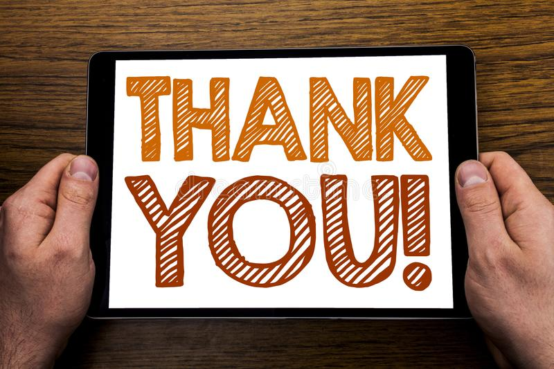 Hand writing text caption Thank You. Business concept for Thanks Message Written on tablet laptop, wooden background with business royalty free stock photos