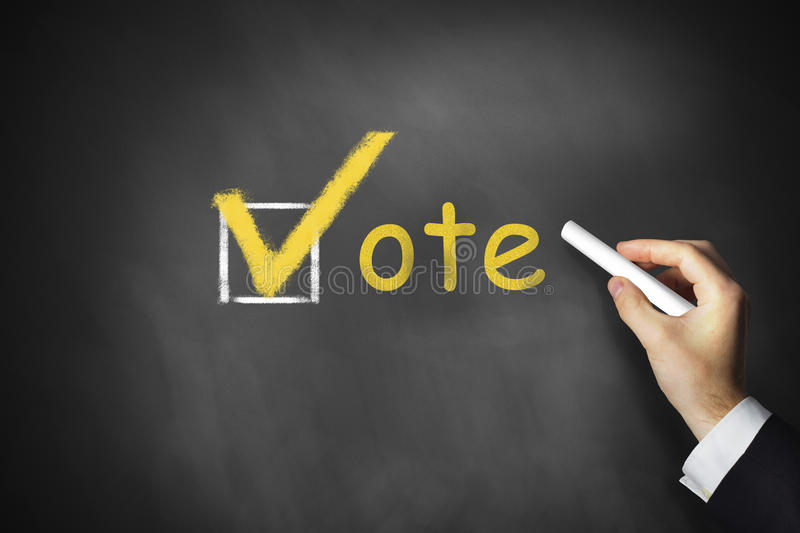 Hand writing vote checkbox on chalkboard royalty free stock photo