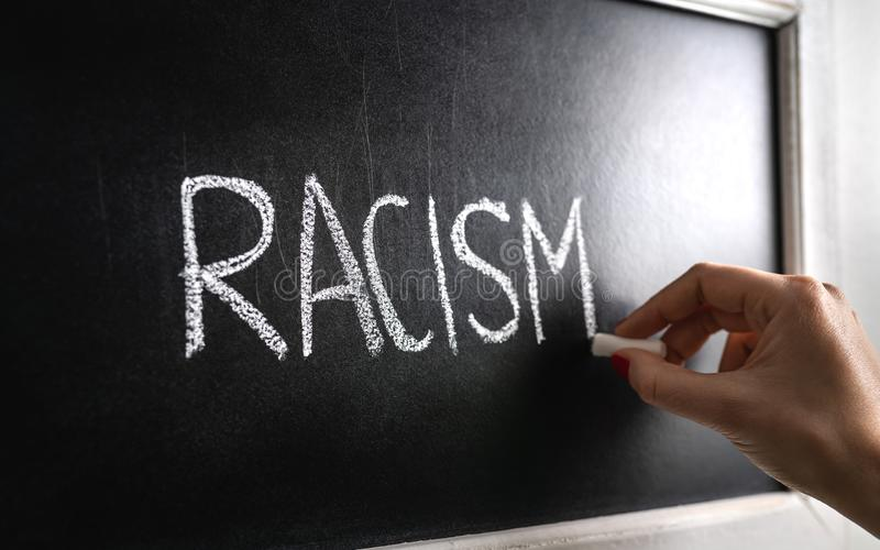 Hand writing the word racism on blackboard. Stop hate. Against prejudice and violence. Lecture about discrimination. Hand writing the word racism on blackboard stock photos