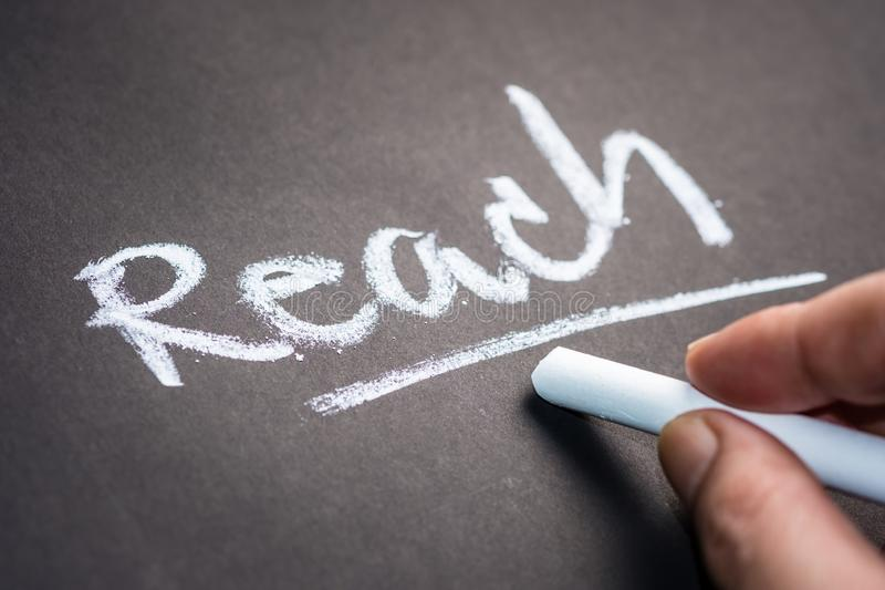 Reach on Chalkboard. Hand writing the word REACH on chalkboard, social media concept stock image