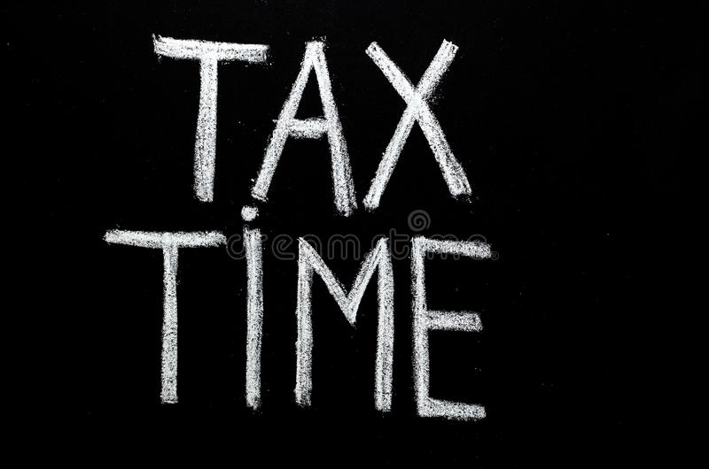 Hand written phrase `tax time` on chalkboard.  royalty free stock photo