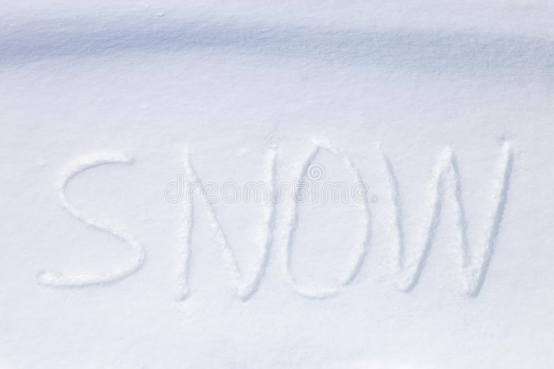 Hand written word `snow` in the snow surface. Natural snow background, hand written word `snow stock image