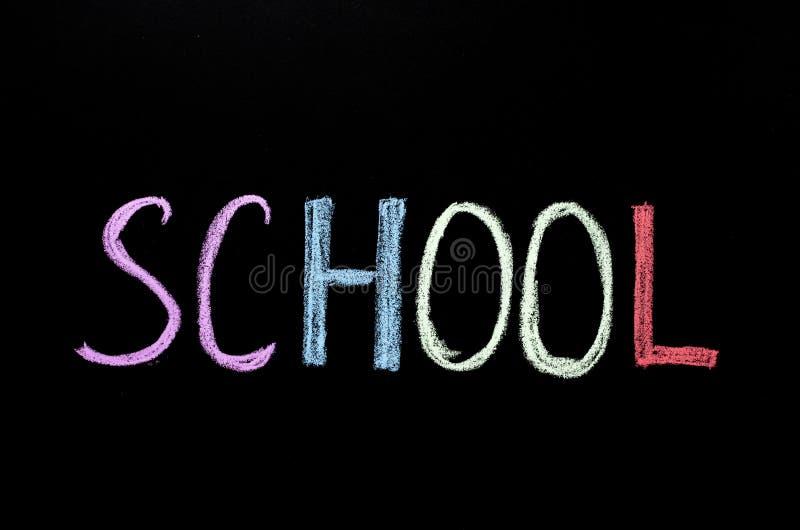 Hand writting word `shcool` on chalkboard.  royalty free stock photography