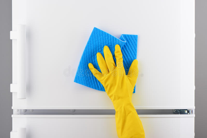 Hand in yellow glove cleaning white refrigerator with blue rag royalty free stock photo