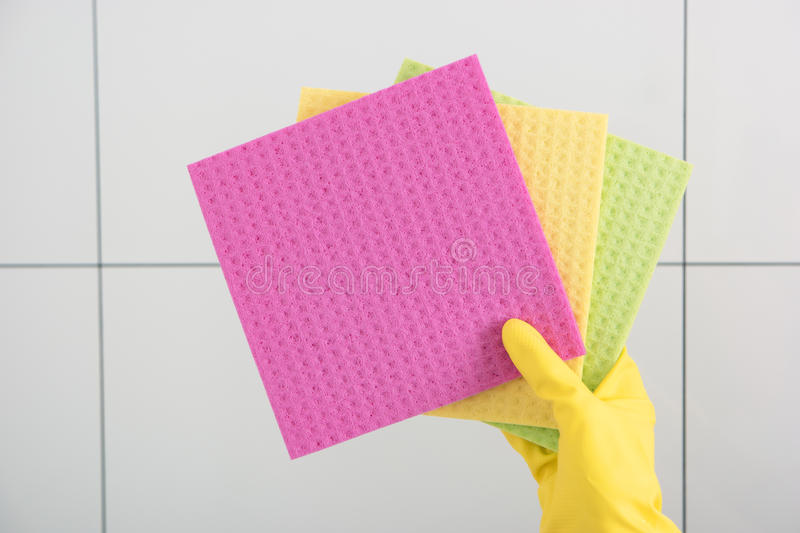 Hand in yellow glove holds multicolored cleaning cloths. stock photography