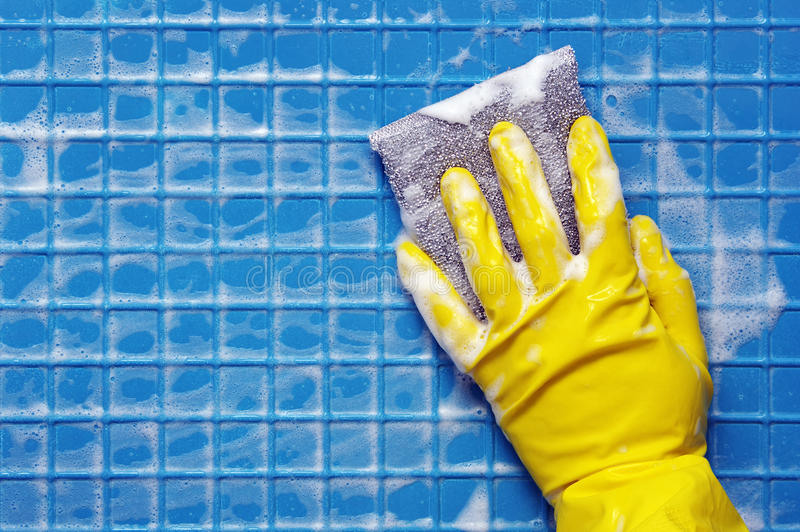 Hand in yellow glove. With silver sponge on blue foam cleaning surface royalty free stock images