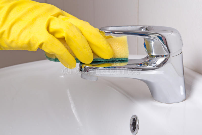 Hand in yellow glove with sponge cleaning sink. Hand in yellow glove with sponge cleaning white sink royalty free stock photography
