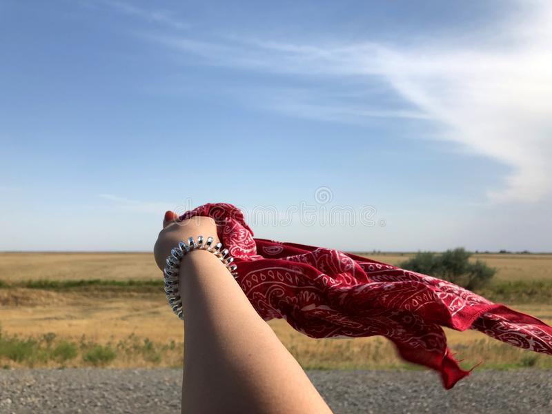 Hand of a young girl with a scarf on the background of nature as a symbol of love. This is a great combination royalty free stock images