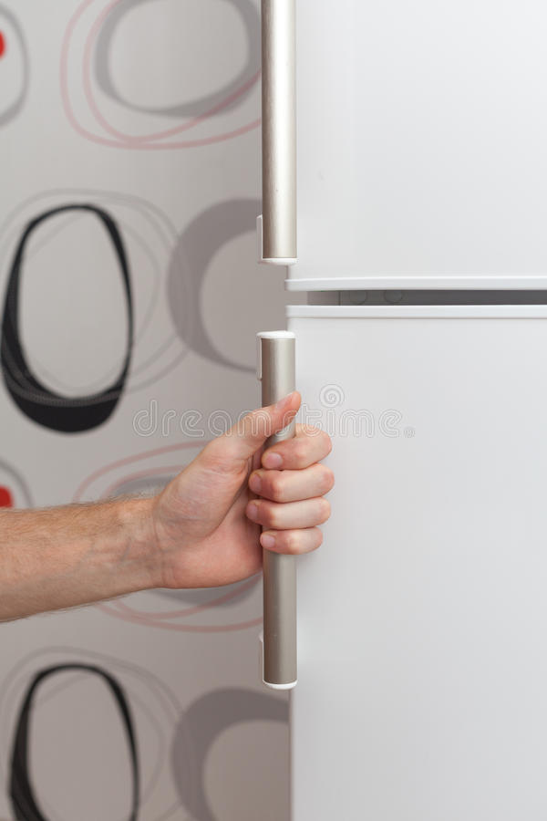 The hand of a young man is opening a freezer door. stock photography