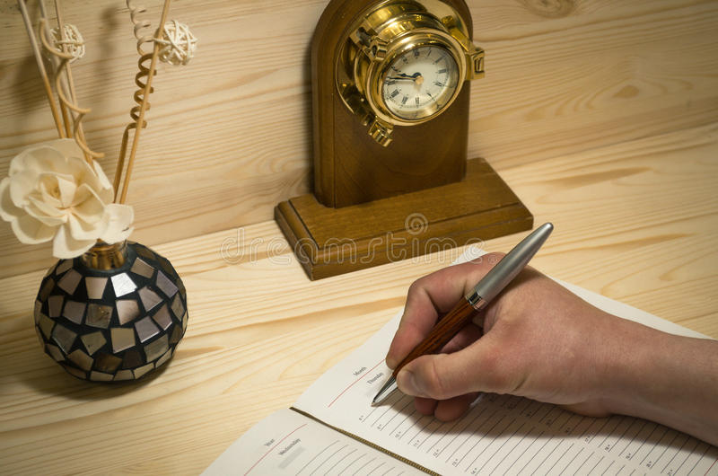Hand of young man writting in diary book on wooden background. stock image
