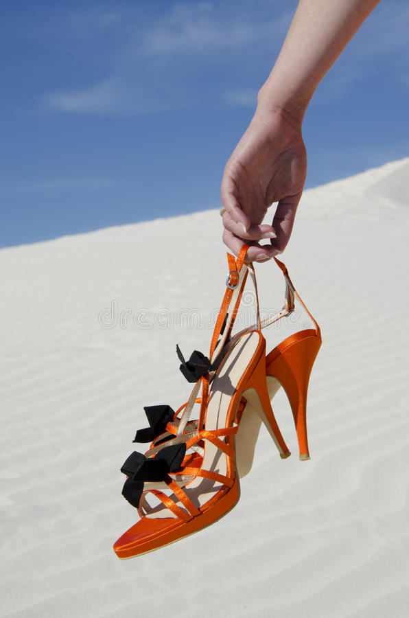 Hand of young woman carrying high heels in dunes stock images