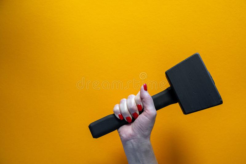 Hand of a young woman holding a black wooden hammer, nails covered with red varnish stock photography