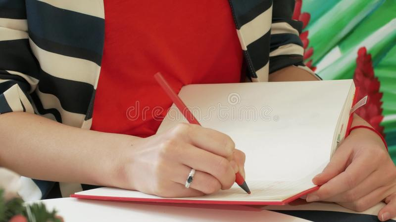 The hand of a young woman in a striped suit takes notes with a pencil in a red notepad. Against the background of drawn green leaves. Girl writer creates a new stock images