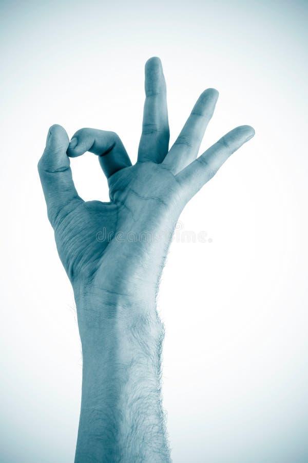 Hand zeigt das OKAYzeichen, das auf einem weißen Hintergrund getrennt wird lizenzfreies stockfoto