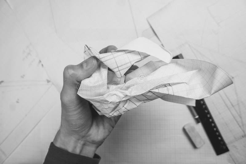Hand zerknittert das Papier über der Tabelle stockbild
