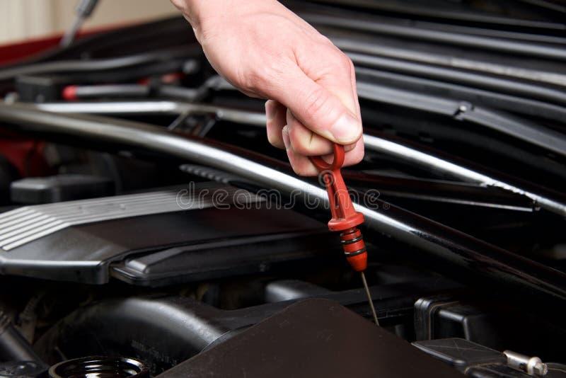 Hand zieht Ölölmessstab in einer sauberen Automotorbucht aus stockbilder