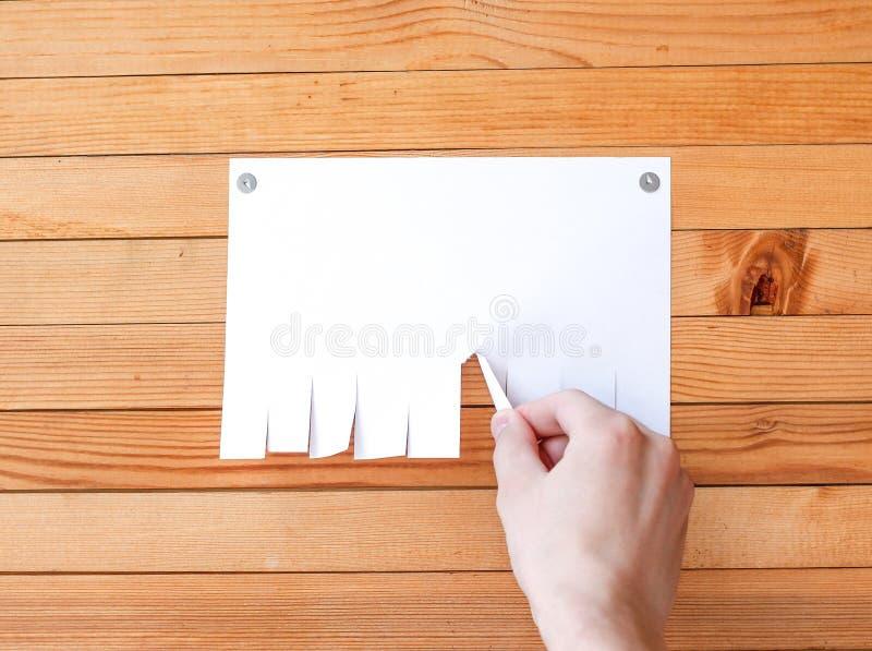 Hand zieht ein Blatt Papier Leere Papieranzeigeneinlegeblätter auf einem wo stockbild