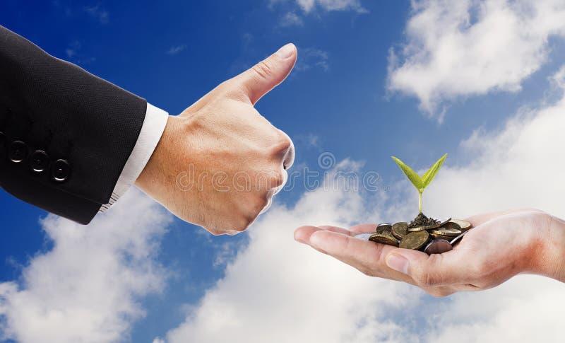 Hand zoals en hand met zaad en muntstukken over wolkenachtergrond stock afbeeldingen