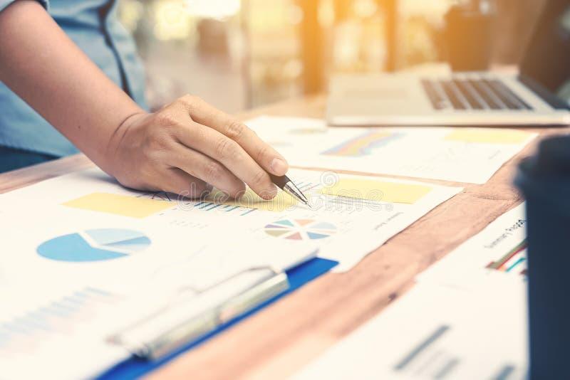 Handaffärskvinnan som pekar pappers- data, analyserar diagrammet på skrivbordet på royaltyfri bild