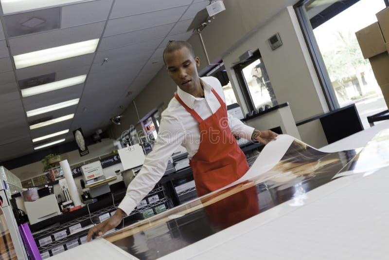 Handarbeider die grote printouts nemen stock fotografie