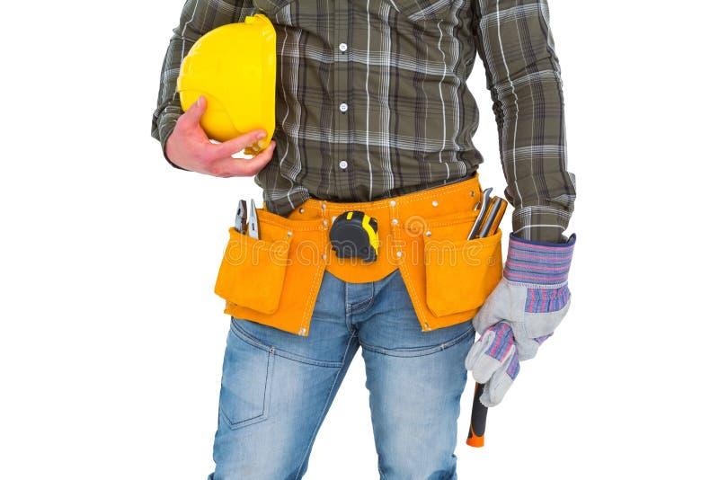 Handarbeider die hulpmiddelriem dragen terwijl het houden van handschoenen en helm stock afbeeldingen
