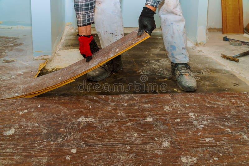Handarbeider die oud vloer gelamineerd parket demonteren stock foto