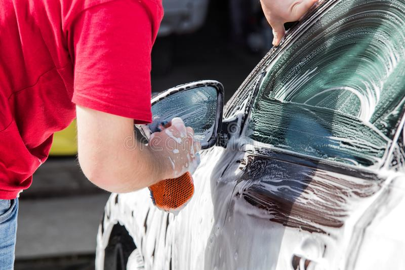 Handautowasserette Mens die zijn auto wast royalty-vrije stock afbeelding
