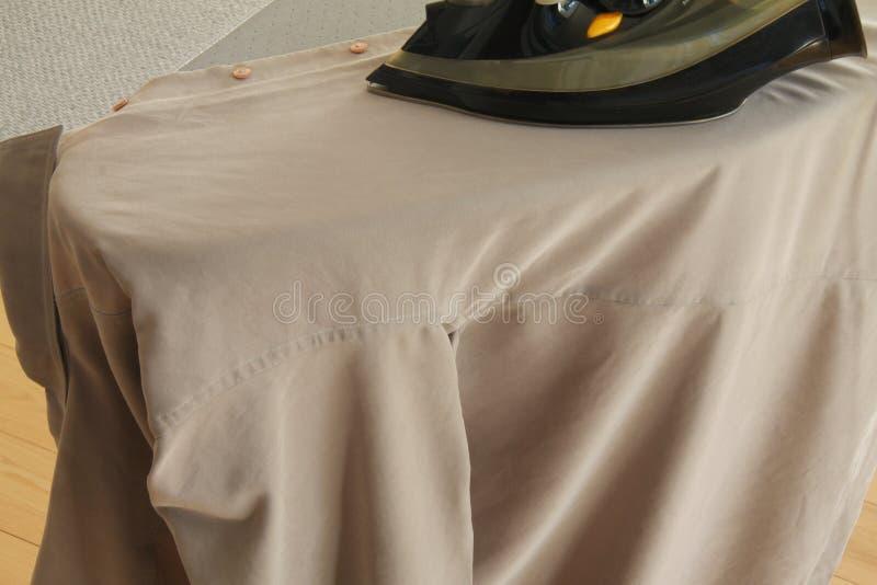 Handbügelndes Hemd an Bord mit modernem Eisen stockbild