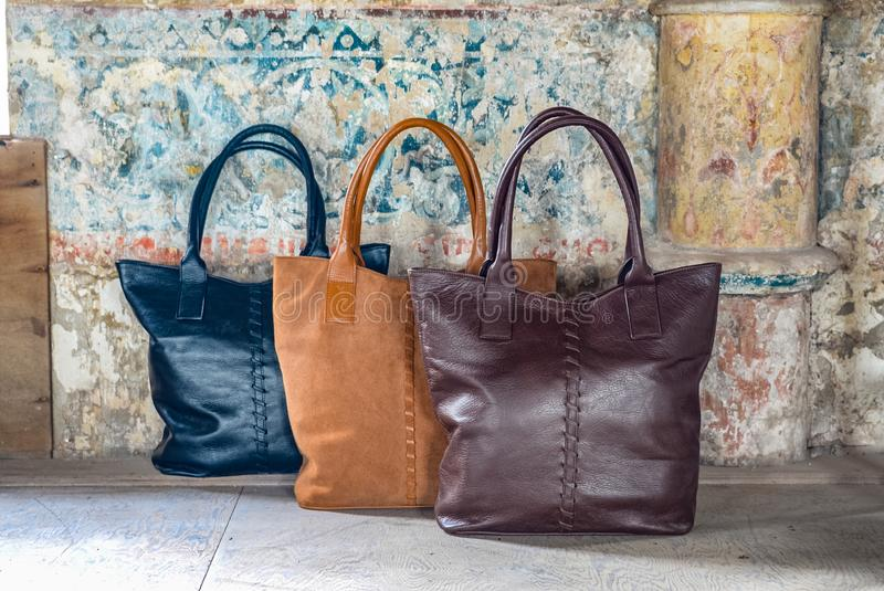 Leather handbags in three colors against beautiful background stock photos
