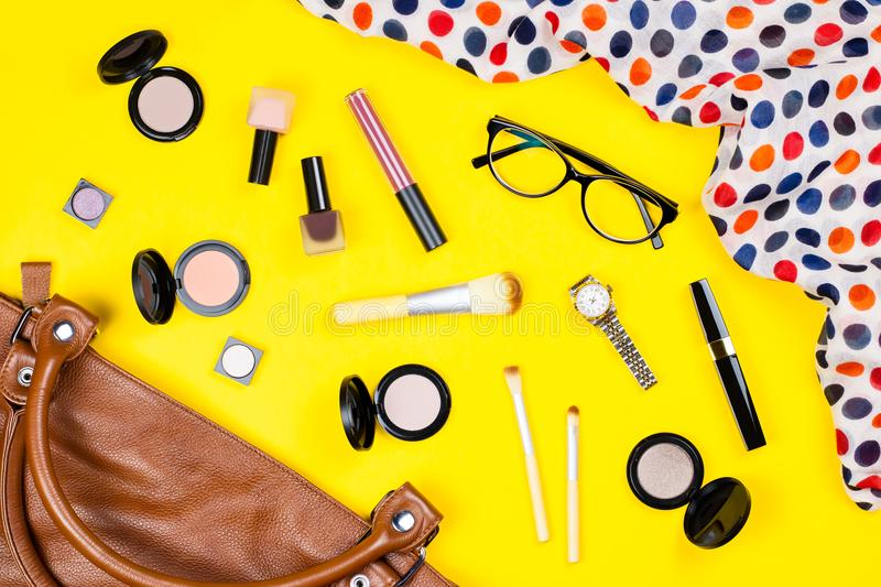 Handbag, make up products, jewelry and accessories. Stylish woman bag stuff flat lay. Top view royalty free stock image