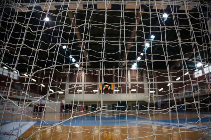 Handball concept. Goal post nets from behind view. Blurred court, athletes and electronic scoreboard background. stock images