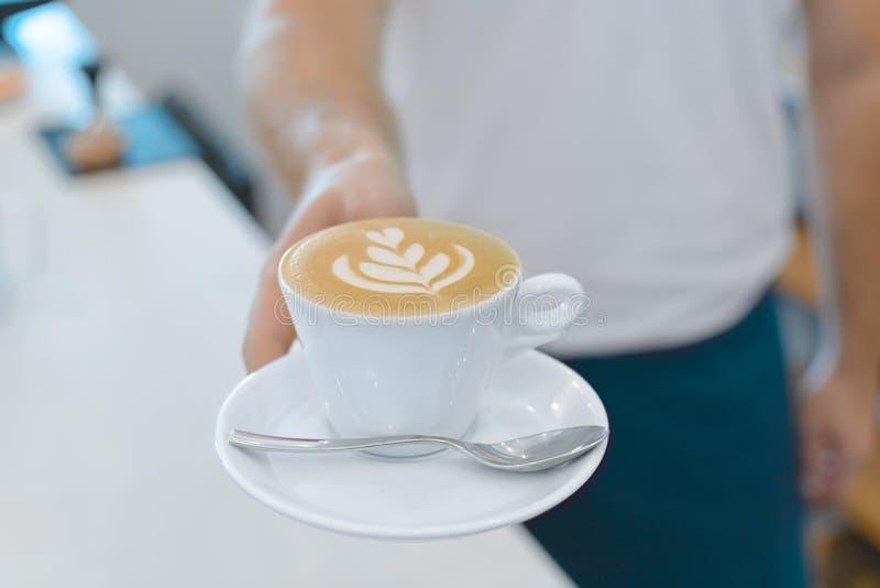 Handbarista holding en het dienen kop van koffie stock foto