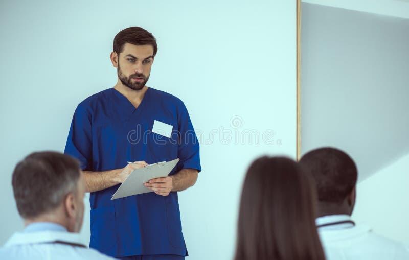 Handbediende arts neemt nota tijdens een gesprek met collega's stock fotografie