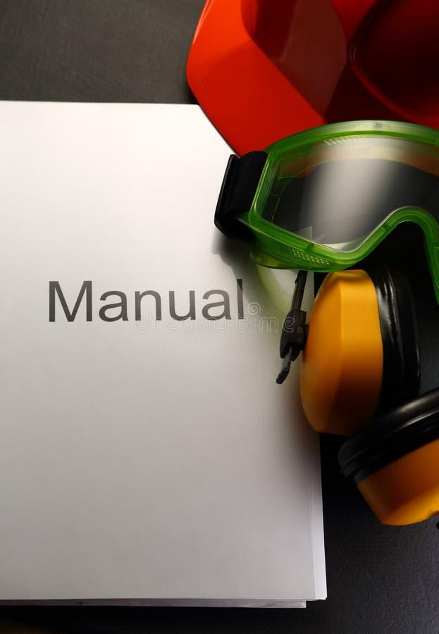 Handboek met helm stock foto