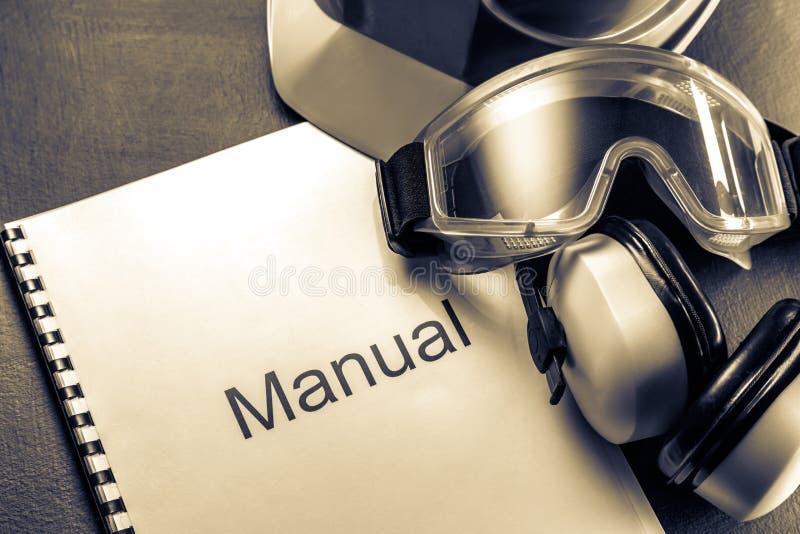 Handboek met helm, beschermende brillen en hoofdtelefoons stock foto