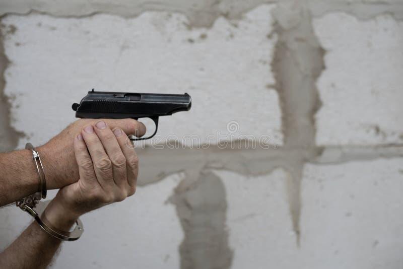 Handbojor håller vapen och är redo att skjuta mot en grå väggbakgrund Kopiera utrymme arkivbilder