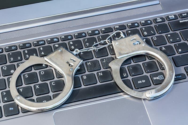 Handbojor som ligger på datortangentbordet som ett symbol för cyberbrott royaltyfri foto